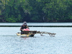 Woman fishing from a canoe in Madang Lagoon, Madang Province, Papua New Guinea